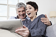 Germany, Bavaria, Munich, Couple using digital tablet at home, smiling - RBF001237
