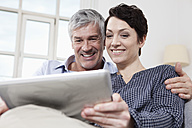 Germany, Bavaria, Munich, Couple using digital tablet at home, smiling - RBF001239