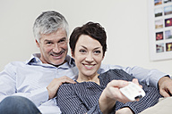 Germany, Bavaria, Munich, Couple changing channels with remote control, smiling - RBF001281