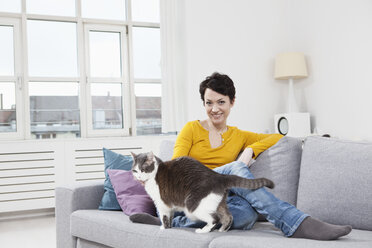Germany, Bavaria, Munich, Portrait of mid adult woman with cat on couch, smiling - RBF001256