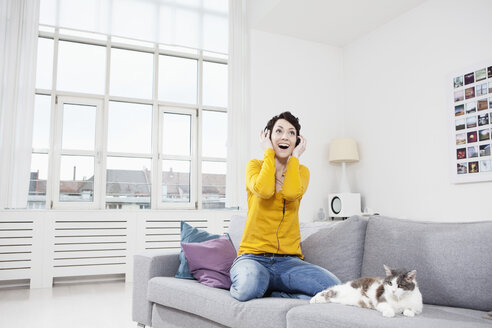 Germany, Bavaria, Munich, Mid adult woman listening music with cat on couch - RBF001244