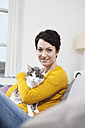 Germany, Bavaria, Munich, Portrait of mid adult woman with cat on couch, smiling - RBF001197