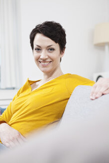 Germany, Bavaria, Munich, Portrait of mid adult woman sitting on couch, smiling - RBF001199