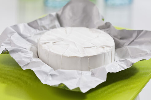 Camembert cheese on paper, close up - CSF018550