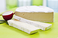 Camembert cheese on chopping board, close up - CSF018552