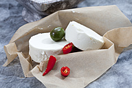 Goat cheese with green olives in olive oil and chili on brown paper, close up - CSF018484