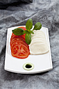 Slices of mozzarella cheese, tomatoes and basil herb on chopping board, close up - CSF018525