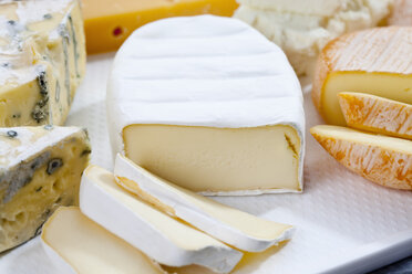 Varieties of cheeses on chopping board, close up - CSF018806