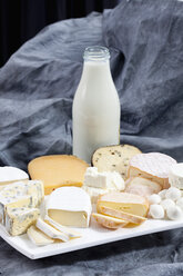 Varieties of cheeses on chopping board with bottle of milk on textile - CSF018807