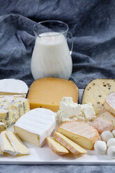 Varieties of cheeses on chopping board with carafe of milk on textile - CSF018747