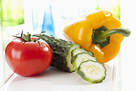 Cucumber, tomato and yellow bell pepper on chopping board, close up - CSF018651
