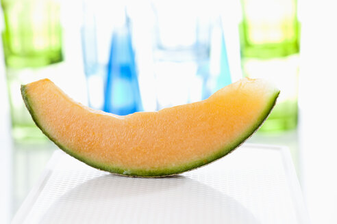 Slice of cantaloupe melon on chopping board, close up - CSF018654
