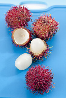 Rambutan fruits on chopping board, close up - CSF018705