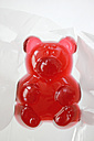 Big red jellybaby in cellophane, studio shot - HSTF000028
