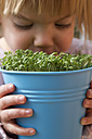Girl holding blue pot with garden cress, close up - LV000013