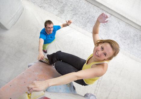 Germany, Bavaria, Munich, Young man helping woman to climb - HSIYF000186