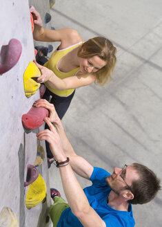 Germany, Bavaria, Munich, Young man helping woman to climb - HSIYF000219