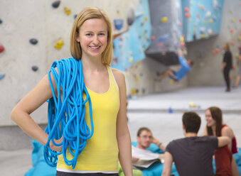 Germany, Bavaria, Munich, Woman with climbing rope while friends relaxing in background, smiling - HSIYF000229