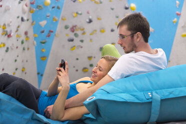 Germany, Bavaria, Munich, Young couple relaxing and using mobile phone, smiling - HSIYF000162