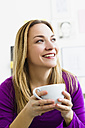 Germany, Bavaria, Munich, Young woman holding tea cup, close up - SPOF000281