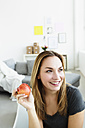 Germany, Bavaria, Munich, Young woman holding apple, looking away - SPOF000308