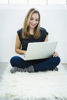 Germany, Bavaria, Munich, Young woman using laptop, smiling - SPOF000331