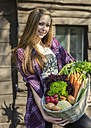 Germany, Portrait of teenage girl holding basket with organic vegetables, smiling - ONF000174