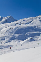 Switzerland, Carmenna, people sking in snow, chair lift in background - WD001693