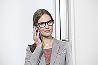 Germany, North Rhine Westphalia, Cologne, Portrait of businesswoman talking on mobile phone, smiling - FMKF000733