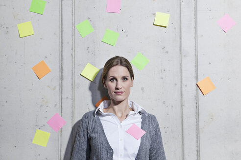 Germany, North Rhine Westphalia, Cologne, Portrait of businesswoman with adhesive notes - FMKF000727