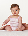 Portrait of baby girl sitting on bed, close up - WWF002898