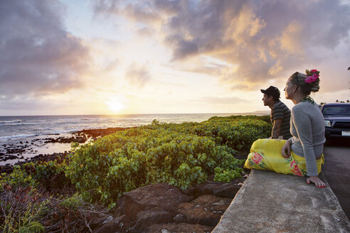USA, Hawaii, Mid adult couple watching sundown by sea - SKF001275