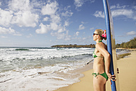 USA, Hawaii, Mid adult woman standing with surfboard  on beach - SKF001277