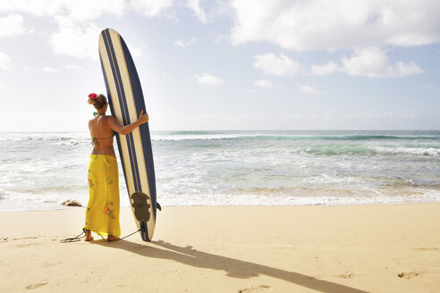 USA, Hawaii, Mid adult woman standing with surfboard on beach - SKF001280