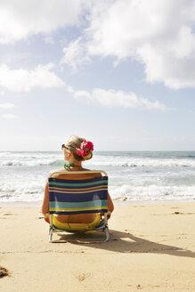USA, Hawaii, Mid adult woman sitting on deck chair at beach - SKF001282