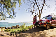 USA, Hawaii, Mid adult couple standing near car - SKF001287