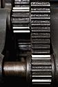 Germany, Bavaria, Cog wheels of printing press in print shop, close up - TC003421