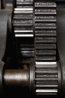 Germany, Bavaria, Cog wheels of printing press in print shop, close up - TC003421