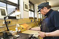 Germany, Bavaria, Mature man looking at copperplate in print shop - TC003431