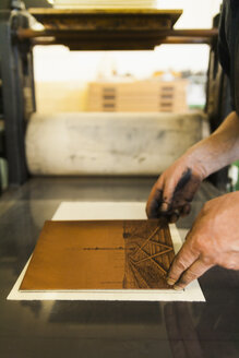 Germany, Bavaria, Mature man picking up copperplate in print shop, close up - TC003442