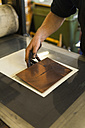 Germany, Bavaria, Mature man picking up copperplate in print shop, close up - TC003443