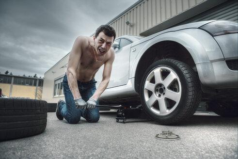 Germany, Bavaria, Kaufbeuren, Mature man changing car tire - DSC000065