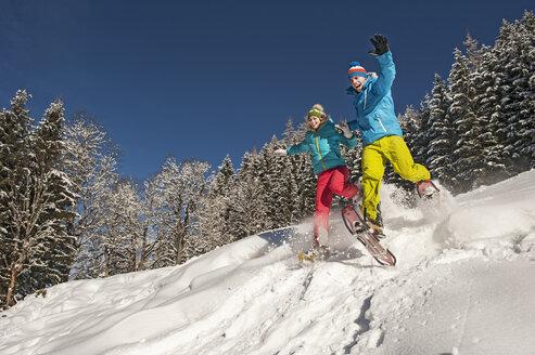 Austria, Salzburg, Young woman and man snowshoeing at Altenmarkt Zauchensee - HHF004580