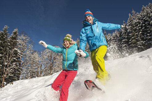 Austria, Salzburg, Young woman and man snowshoeing at Altenmarkt Zauchensee - HHF004579