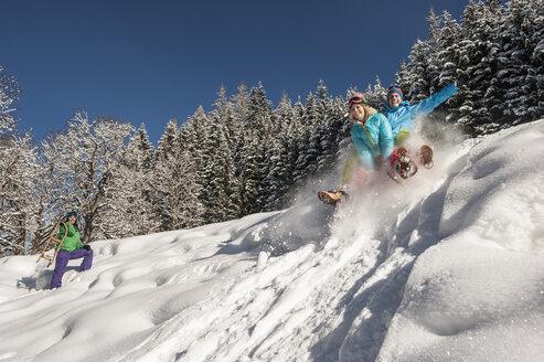 Austria, Salzburg, Young man and women with sledge in snow at Altenmarkt Zauchensee - HHF004587