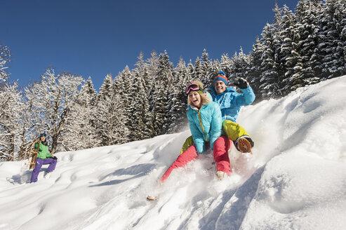 Austria, Salzburg, Young man and women with sledge in snow at Altenmarkt Zauchensee - HHF004586