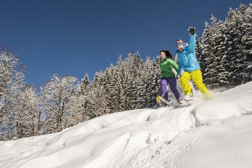 Austria, Salzburg, Young woman and man snowshoeing at Altenmarkt Zauchensee - HHF004583