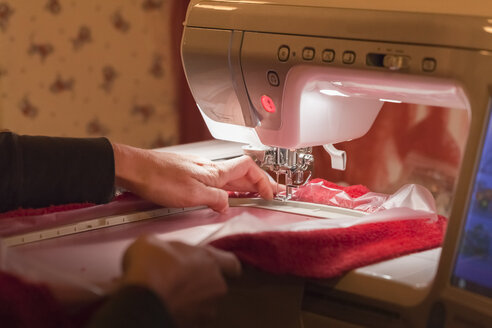 Germany, Laupheim, Mature woman embroidering with semi-professional embroidery machine - HAF000074