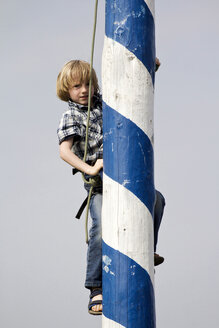 Germany, Bavaria, Boy climbing maypole - SAR000031