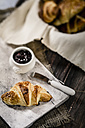 Croissants and jam on wooden table, studio shot - SBDF000155